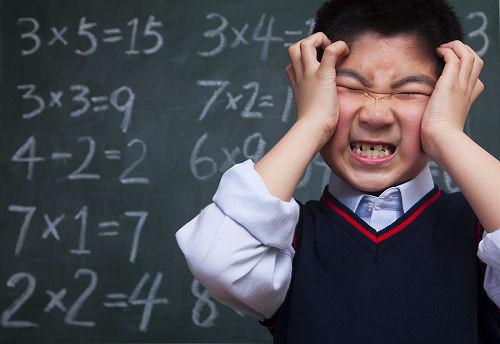 Schoolboy in front of blackboard holding head